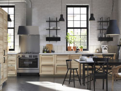 A large black kitchen with doors and drawers in black wood effect combined with glass-doors in smoked tempered glass.