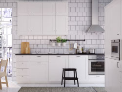 A white medium size kitchen with black worktops, handles and knobs. Combined with stainless steel extractor hood, oven and microwave oven.