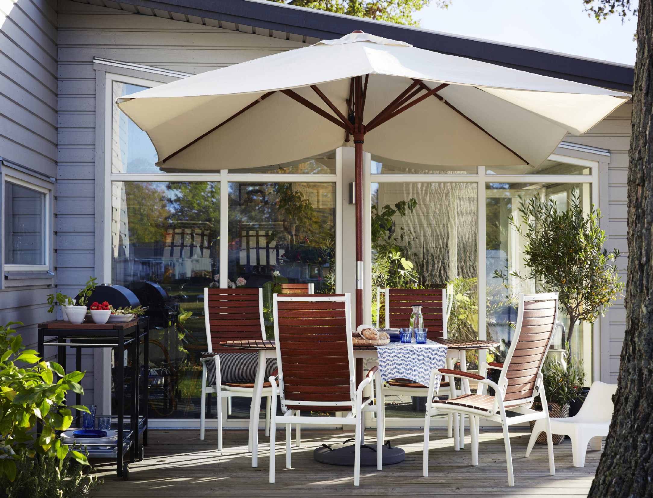 A large terrace furnished with a table, that seats up to six people, and four reclining chairs, all in solid eucalyptus with white aluminium legs. Completed with a large rectangular parasol and a trolley with a charcoal barbecue.