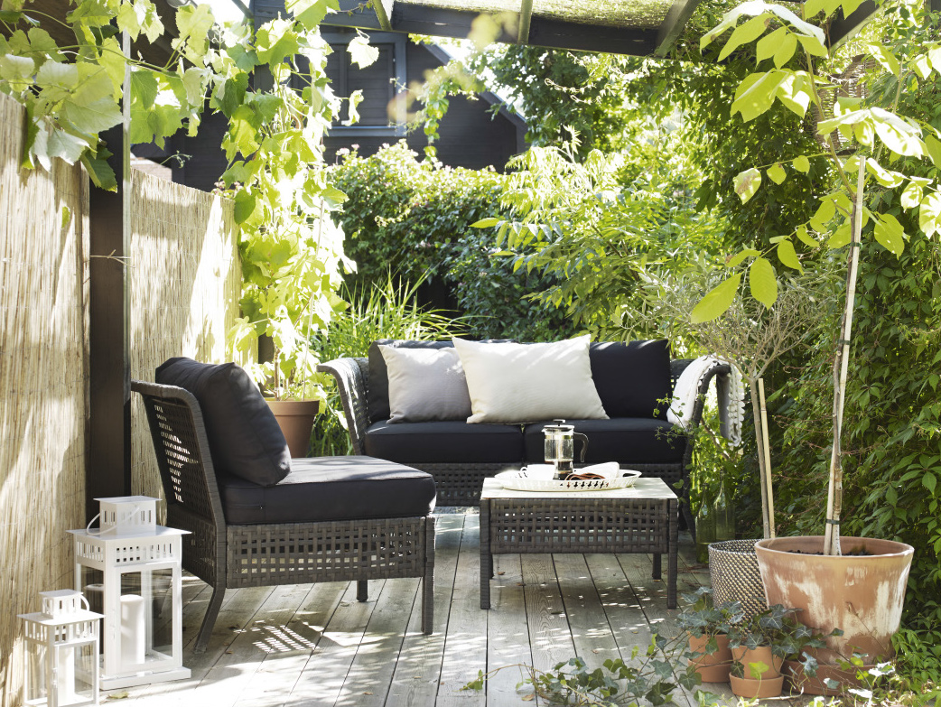 A small terrace furnished with a coffee table, a two-seat sofa and an easy chair, all in black-brown plastic. Completed with cushions in black, beige and grey.