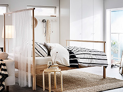 A light bedroom furnished with a bed in white stained oak combined with white chest of drawers and bedside tables.