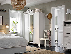 A small bedroom furnished with a wardrobe with two white doors and one mirror door. Shown together with a white bed and a chest of drawers.
