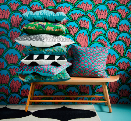 A bench with a pile of cushions on bold colours and patterns.