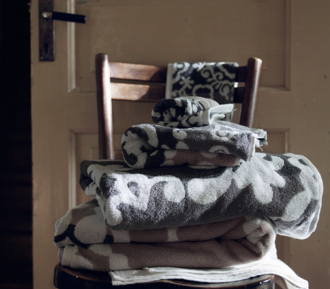 A chair with a pile of towels in different sizes.