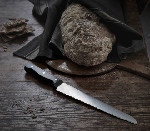 A bread knife shown together with a newly baked loaf of bread.