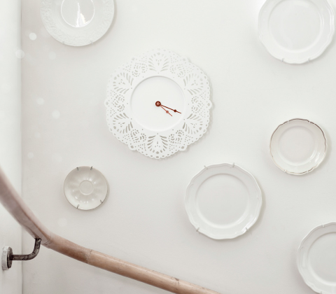 A white wall clock with a lace pattern.