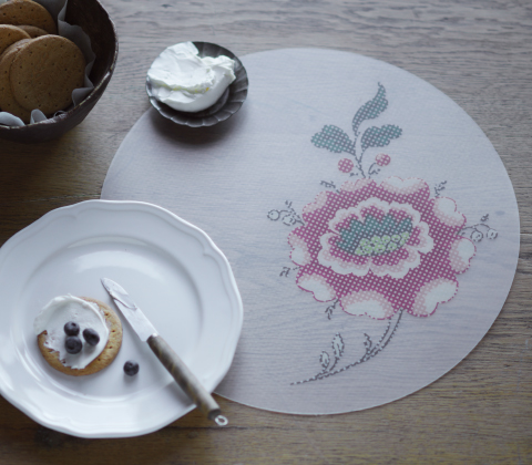 A round place mat with a big pink flower.