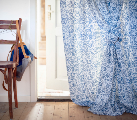 A curtain with a blue/white floral pattern used as a drape in a doorway.