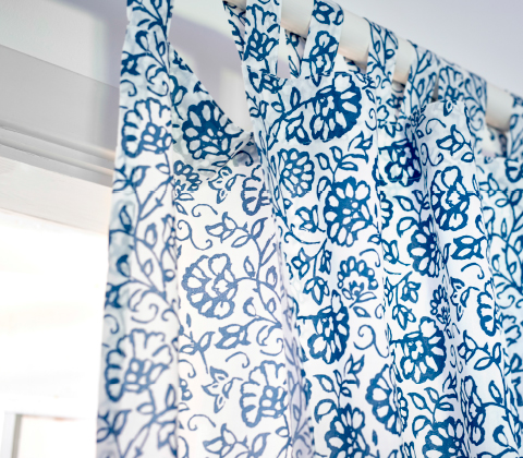 Close-up of a curtain with tabs at the top in a blue/white floral pattern.