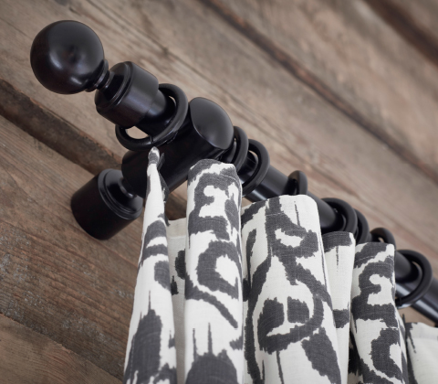 Close-up of a black curtain rod with finials and curtain rings with clips.