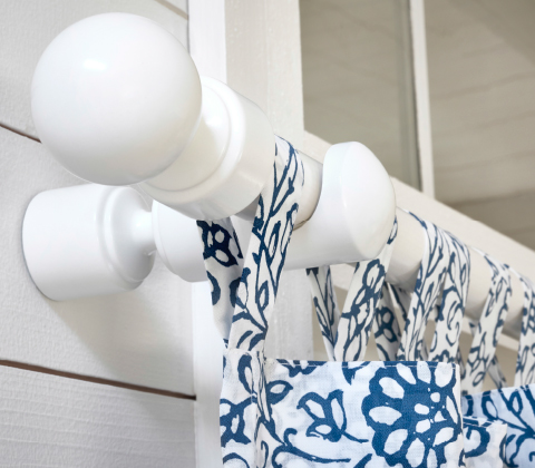 Close-up of a white curtain rod with finials and a floral curtain with tabs at the top.