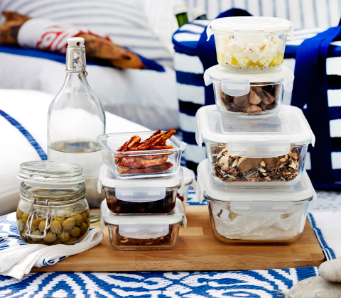 Stacked food containers in clear glass with plastic lid. Filled with cheese, mushrooms and olives.
