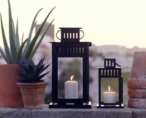 Two black lanterns, one large and one small, with lit block candles.