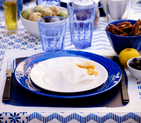 A ready laid table in white and blue with plates, bowls and glasses.