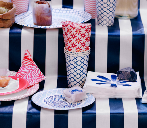 A display of paper cups, paper plates and napkins in blue/white and red/white.