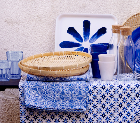 A display of  bamboo bread baskets shown together with blue/white tablecloths, mugs, glasses and trays.
