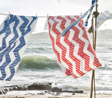 Beach towels in blue/white and red/white, hanging on a clothes line.