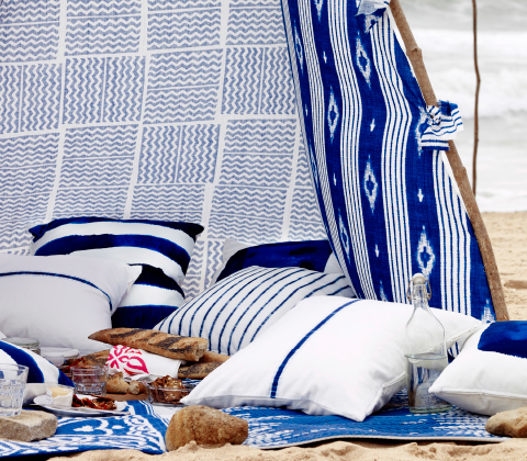 A tent on the beach, made of fabric with lots of white/blue cushions inside.