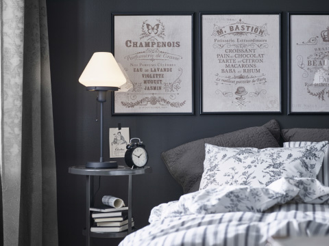 A grey and white bedroom with ephemera style posters on the wall