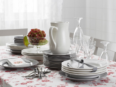 Stacks of white and grey plates and bowls on a table with a floral tablecloth