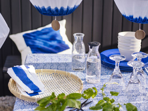A close-up of assorted glassware on a table with a blue and white tablecloth