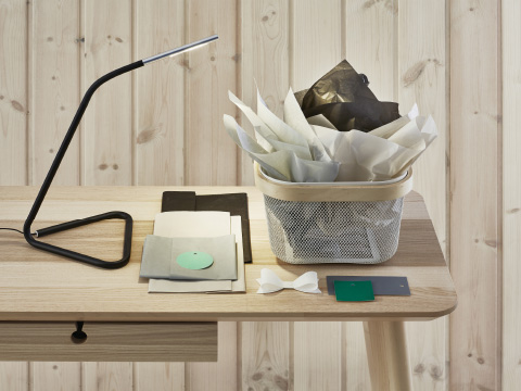 A work lamp and bin filledwith paper on a wooden desk