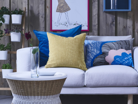 A white sofa filled with blue and yellow cushions