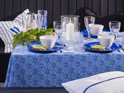 A table with a blue and white tablecloth set with blue plates and white bowls
