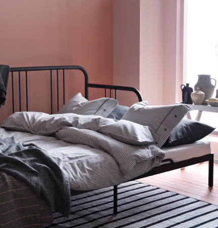 A day-bed in black metal shown as a bed for two with blue/white striped bedlinen.