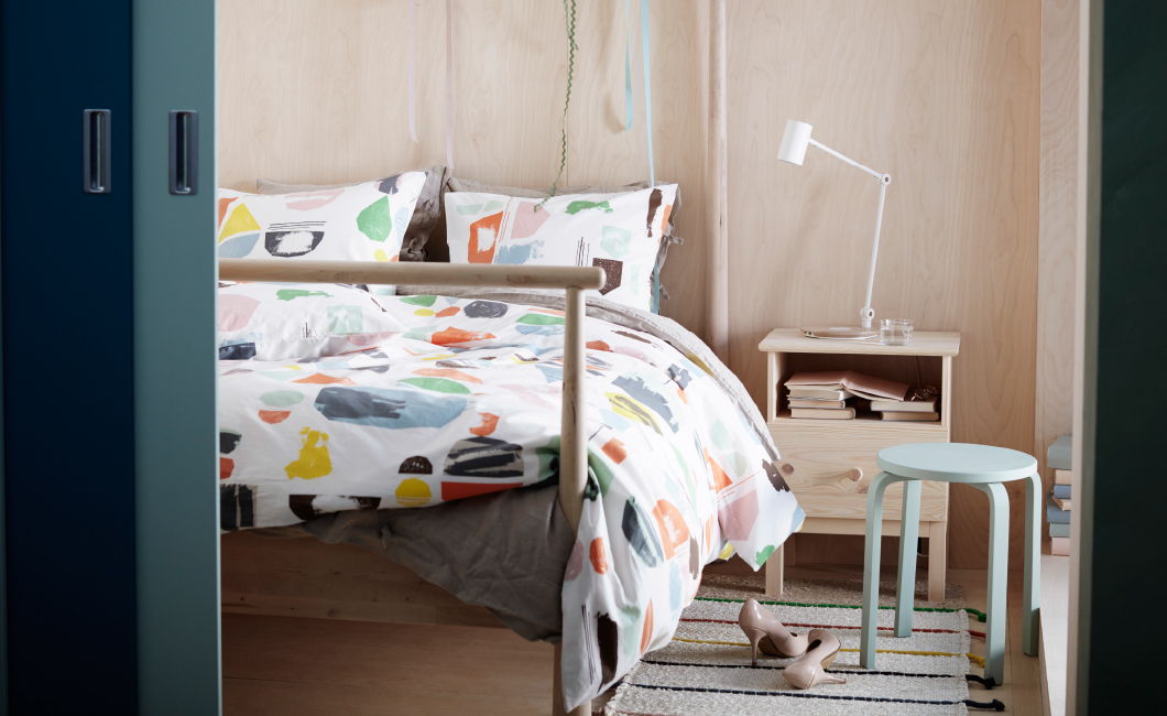 Quilt cover and pillowcases with pattern of paint brush strokes and paper clipings in pastel colours.