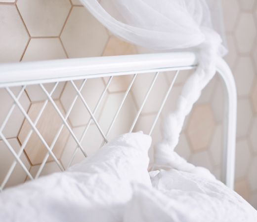 A close-up of a white headboard with square patterned metal bars.