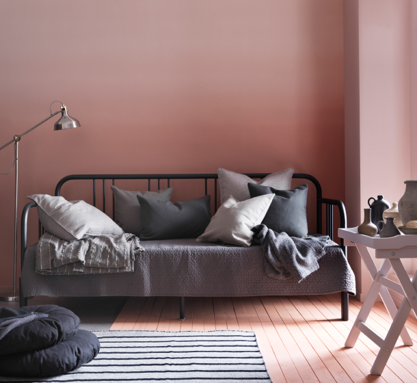 A day-bed in black metal shown as a sofa filled with grey cushions.
