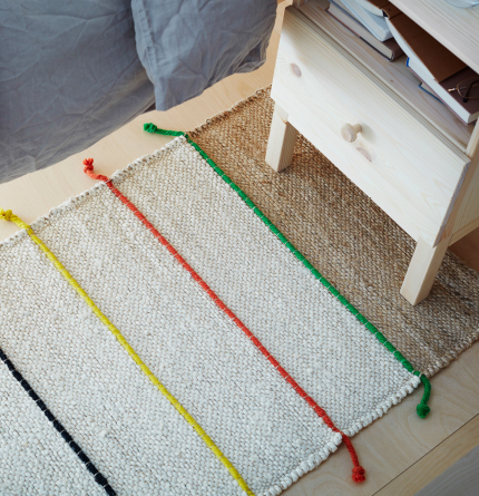 A natural-coloured hand-woven jute rug with coloured bands.