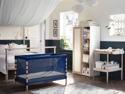 A blue cot with fine-meshed bedsides inside the parent's bedroom. Shown together with a chaging table and a wardrobe in white and beech.