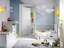A children's bedroom furnished with a white crib with two drawers, a changing table and a storage bench with a large drawer on castors.