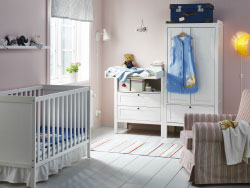 A nursery with a cot, changing table and wardrobe, all in white combined with an armchair in red/beige.