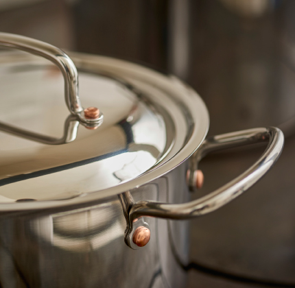Close-up of a stainless steel pot with rivets on the handles.