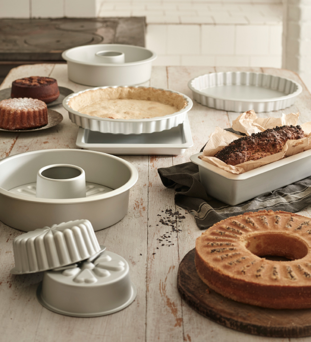 A table with baking tins for pies, sponge cakes and bread in different shapes and sizes.