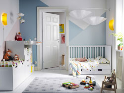 A children's bedroom furnished with a white cot with two drawers, a changing table and a storage bench with a large drawer on castors.