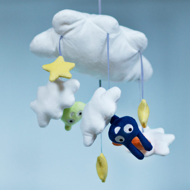 A mobile with white clouds and small animals and stars.