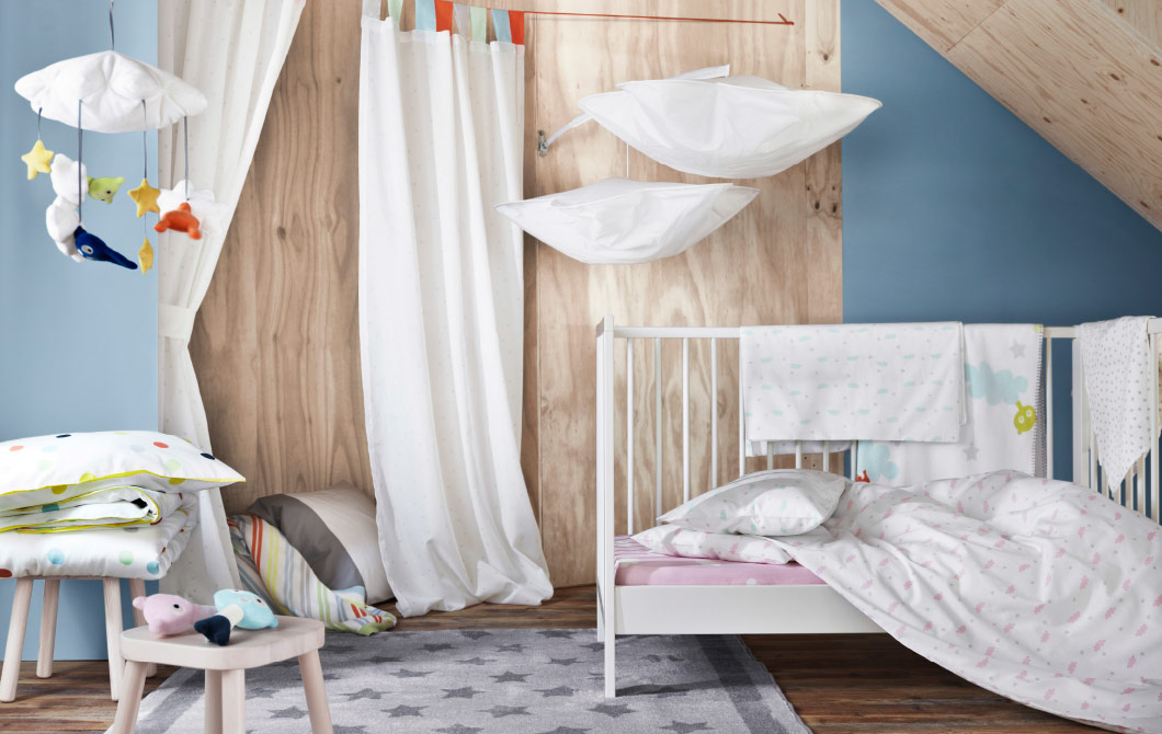 A display of a collection consisting of children's bedlinen, a bed canopy, curtains and a mobile.