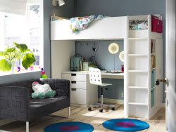 A boy's room with a white loft bed combination that includes a desk, chest of drawers and a wardrobe. Shown together with a small gray sofa and braided round rugs in turquoise/lilac.