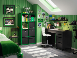 A boy's bedroom furnished with a black desk combined with a drawer unit on castors and a green shelving unit with black storage boxes.