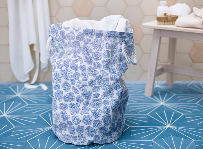 A textile laundry bin with light blue floral pattern and white rope handles.