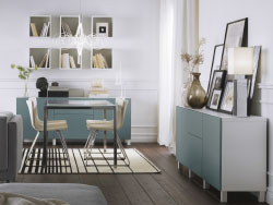A living room with a dining area furnished with a dining table in chrome and white glass shown together with chairs in chrome and white leather. Storage cabinets in white with grey-turquoise doors and drawer fronts.