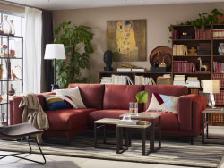 A medium sized livingroom furnished with a rust-red sofa combination that seats three people. Shown together with three nest of tables and a darkbrown armchair made of natural fibres.