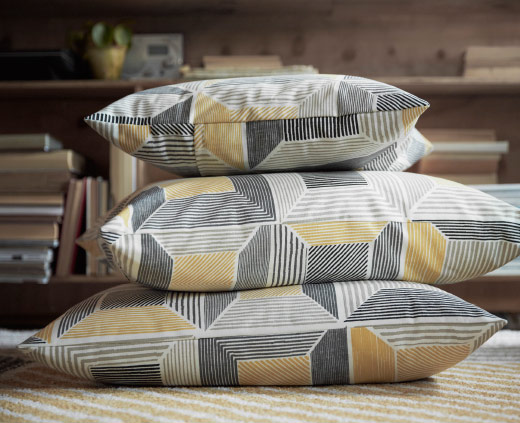 Cushions made of a metre fabric in grey and yellow with a geometric pattern.