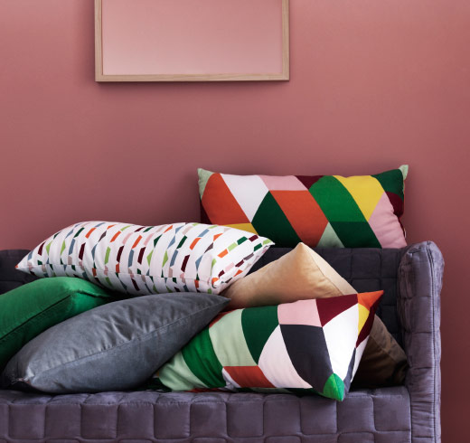 A sofa with cushions in colourful geometric patterns.