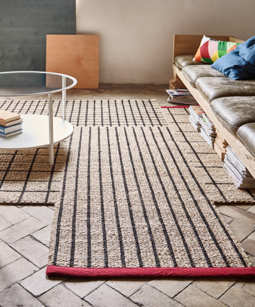 A natural-coloured jute rug with black squares, stripes and red edging.