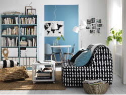 A small livingroom furnished with a sofa-bed for two in a black/white cover. Shown together with a white side table on castors, a modern rocking chair made of banana fibres and light turquoise bookcases.